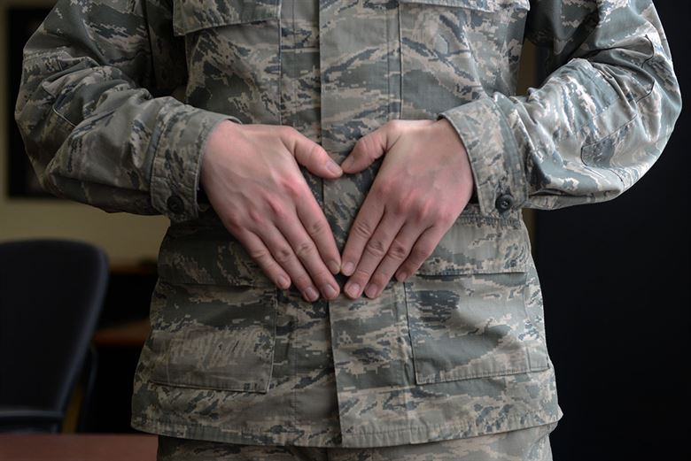 Soldier holding his stomach with his hands.