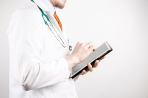 Doctor with a tablet speaking to a patient.