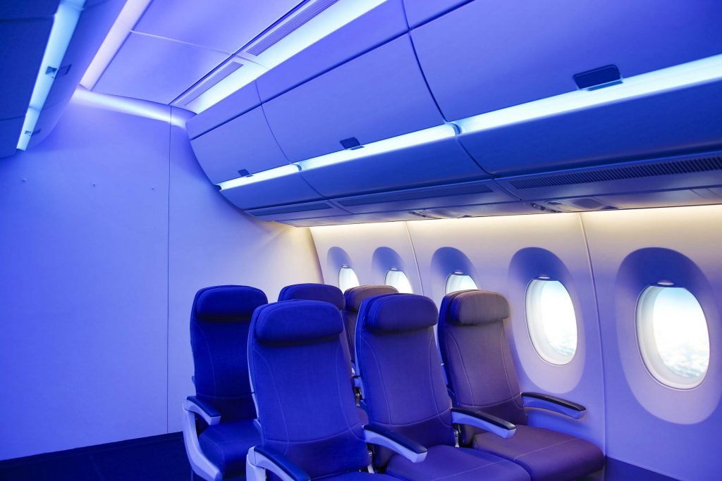 Airplane interior with blue lighting.